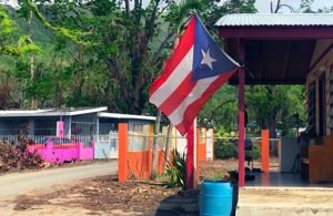 The Puerto Rican flag flying in a village affected by disaster.